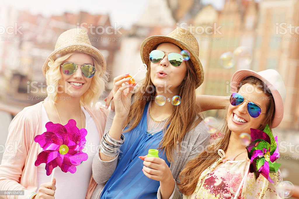 Group of friends blowing soap bubbles stock photo