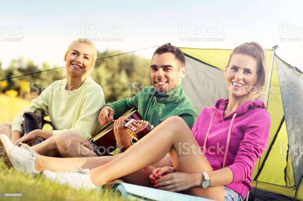 Group of friends camping in forest and playing guitar stock photo