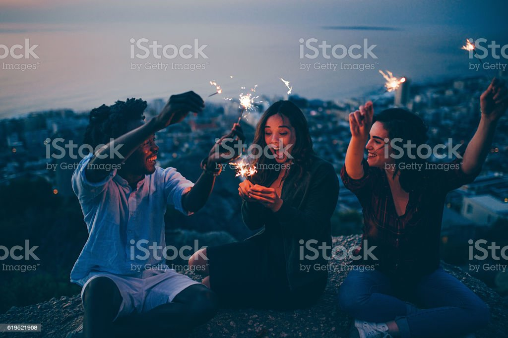 Group of friends celebrating with sparklers at night stock photo