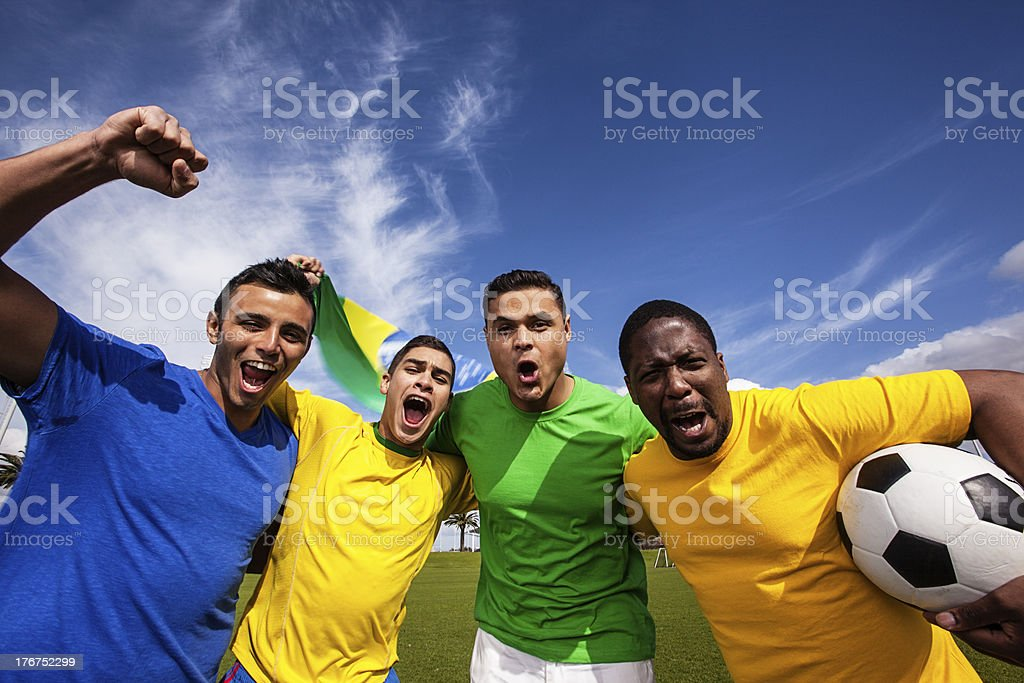 Group of friends cheering for Brazil's soccer team stock photo