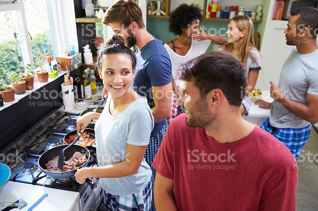 Group Of Friends Cooking Breakfast In Kitchen Together stock photo