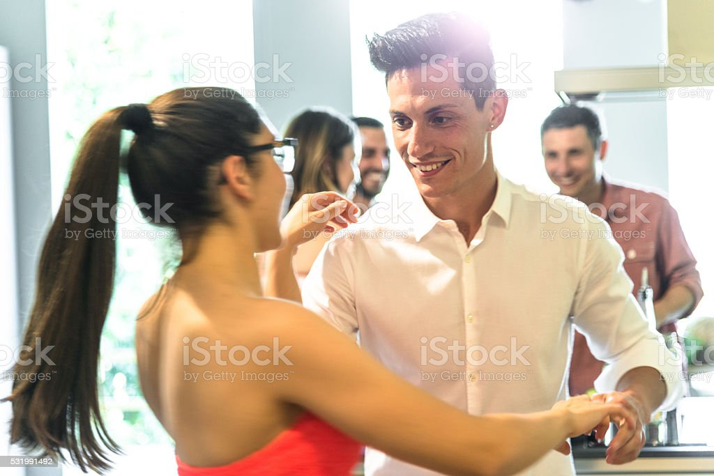 group of friends dancing on the party on the kitchen stock photo