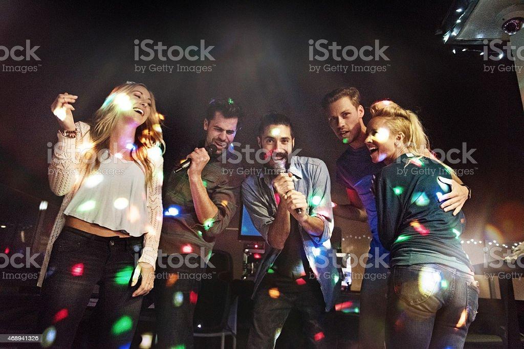 Group of friends doing karaoke stock photo