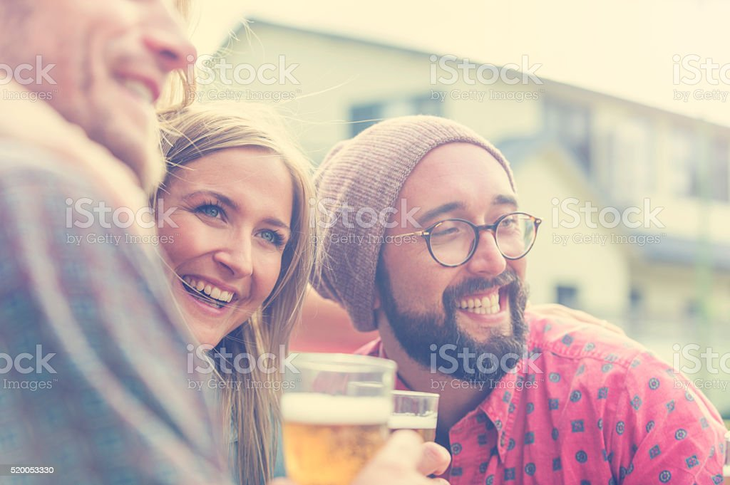 Group of friends drinking beer and having fun. stock photo