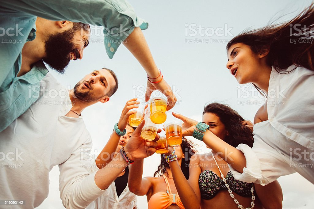 Group of friends drinking beer at beach party stock photo