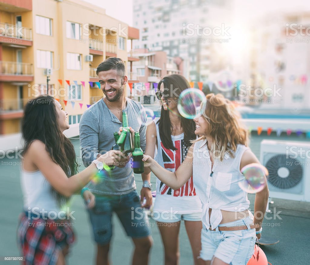 Group of friends drinking beer on the rooftop stock photo