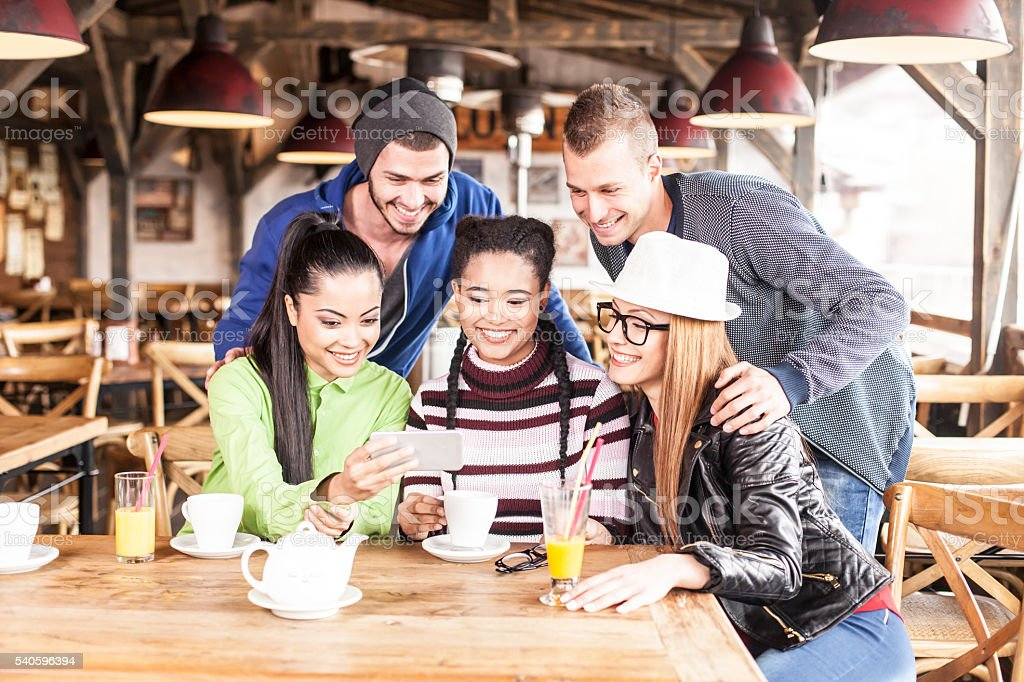 Group of friends drinking coffee together and having fun stock photo