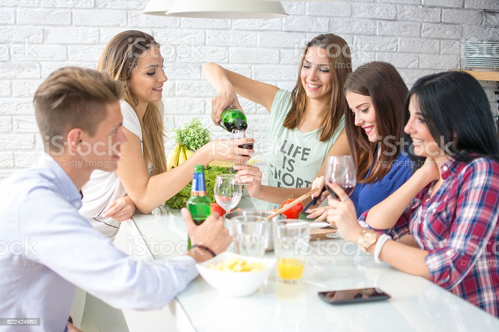 Group of friends drinking red wine and preparing a meal. stock photo