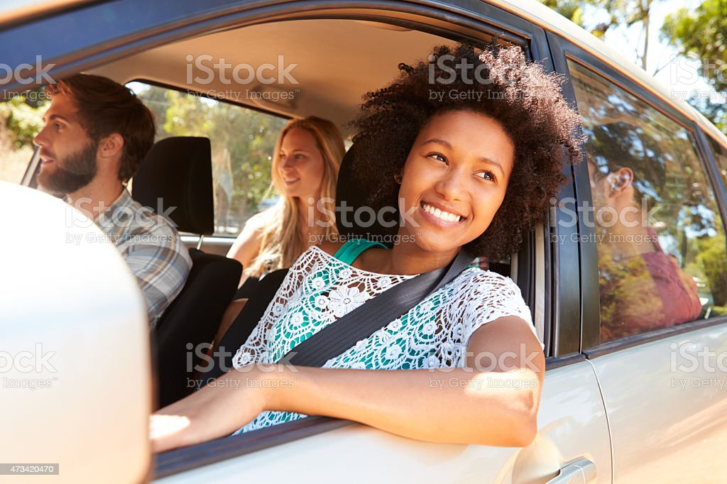 A group of friends driving in a car together stock photo