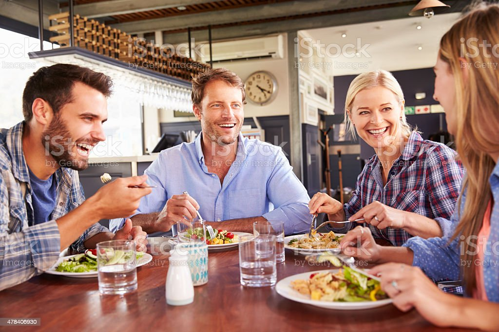 Group of friends eating at a restaurant stock photo