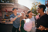 Group of friends eating candyfloss at fairground