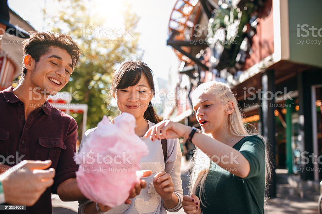Group of friends eating cotton candy in amusement park stock photo