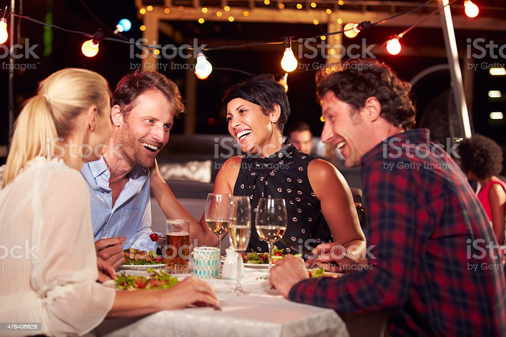 Group of friends eating dinner at rooftop restaurant stock photo