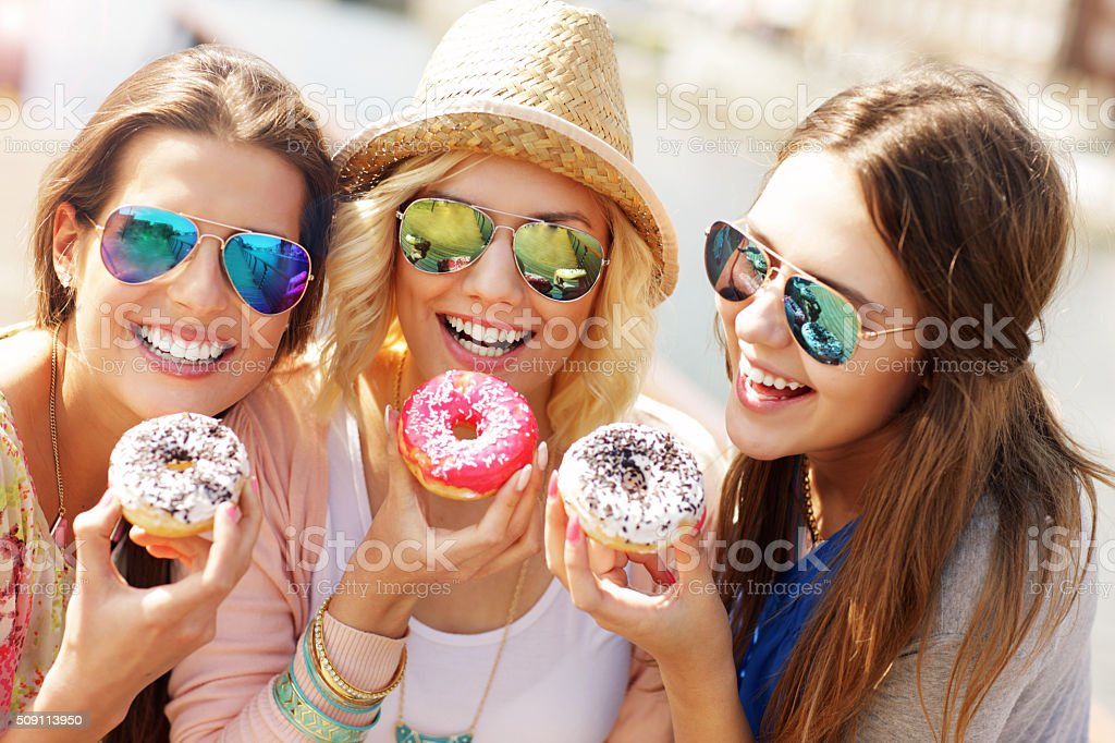 Group of friends eating donuts in the city stock photo
