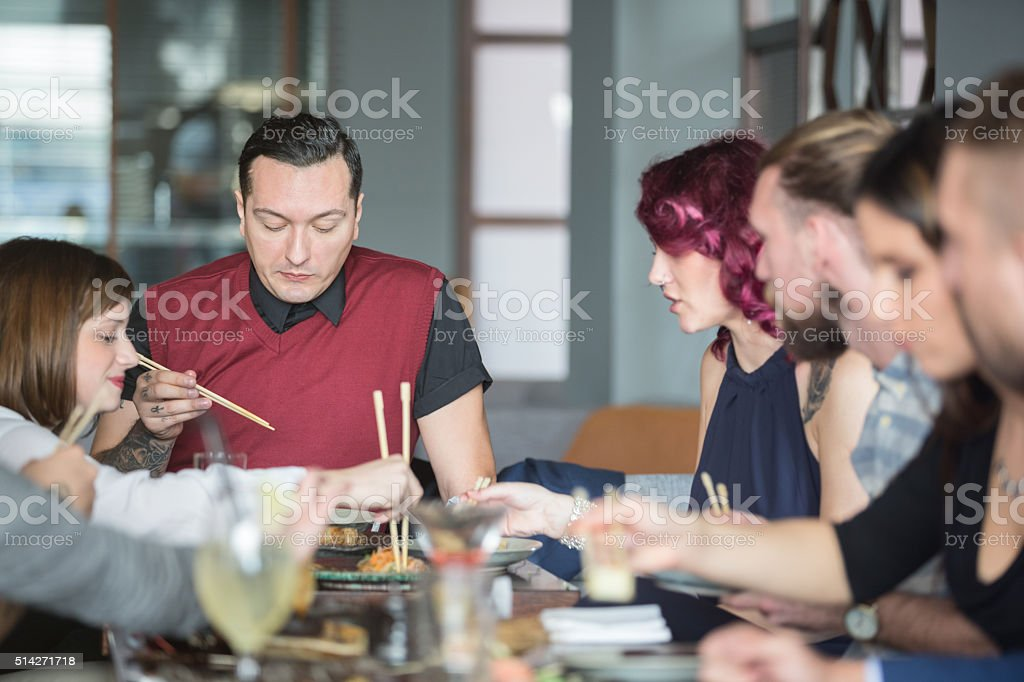 Group of friends eating in restaurant stock photo