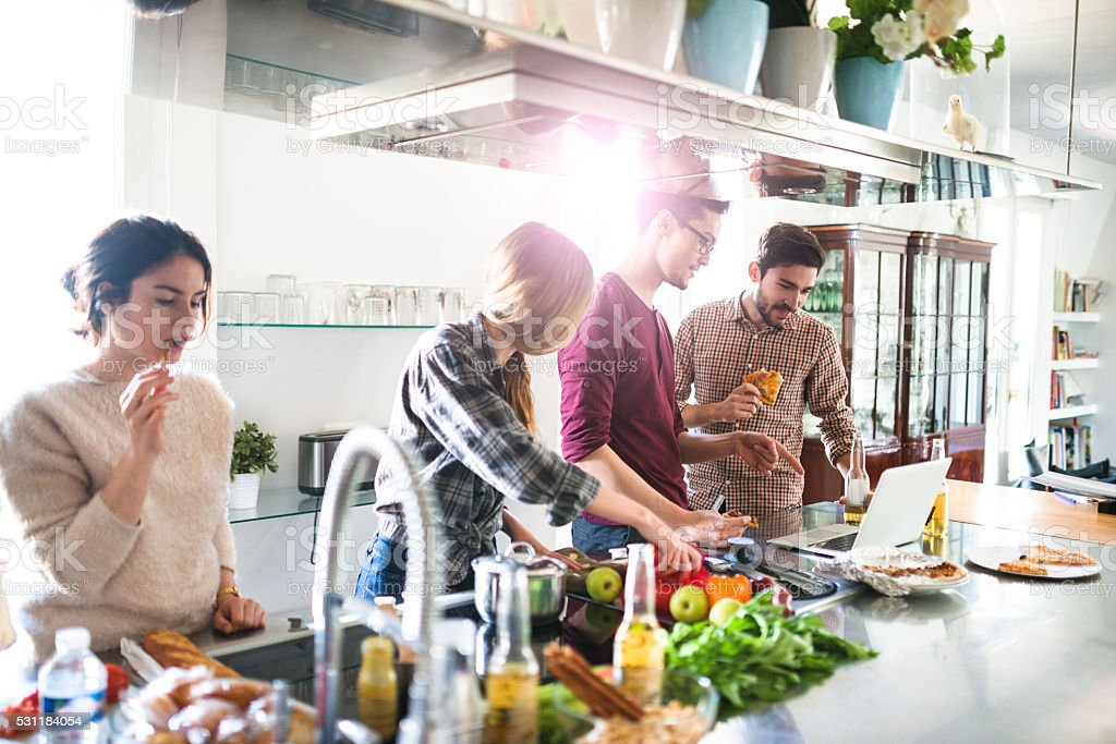 group of friends eating on the kitchen and preparing food stock photo