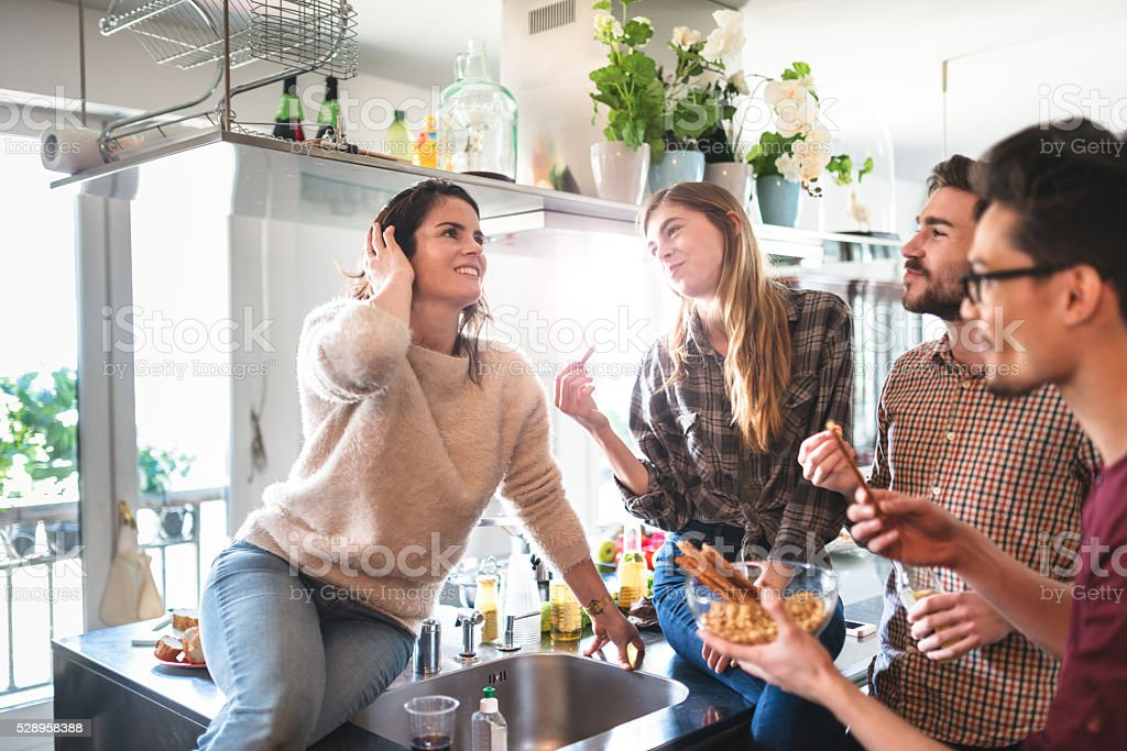 group of friends eating on the kitchen for the party stock photo