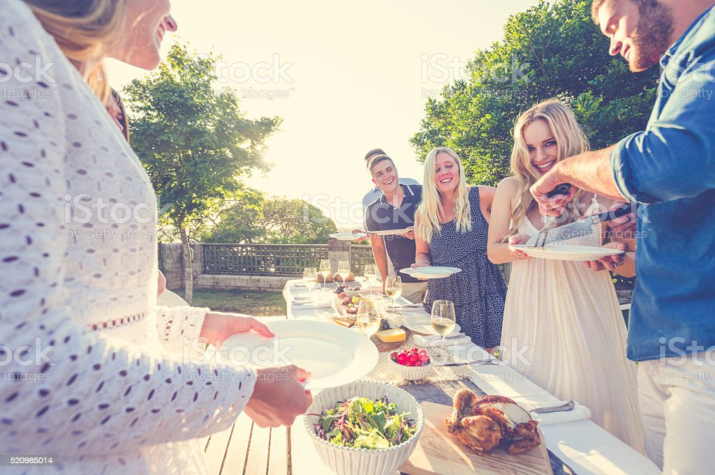 Group of friends eating outdoors. stock photo