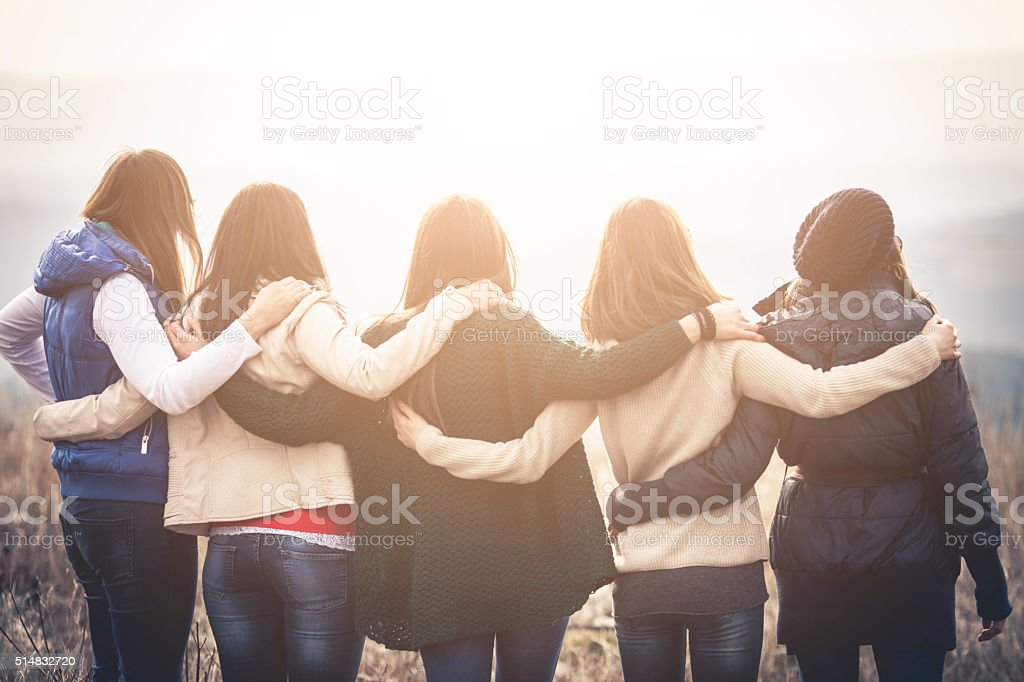 Group of friends embracing outdoors stock photo