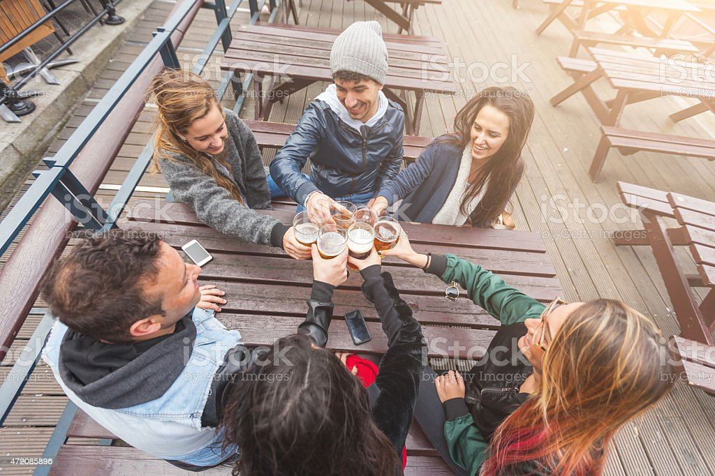 Group of friends enjoying a beer at pub in London stock photo