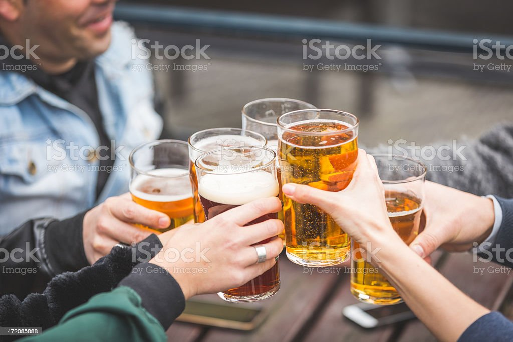 Group of friends enjoying a beer outside a pub in London stock photo