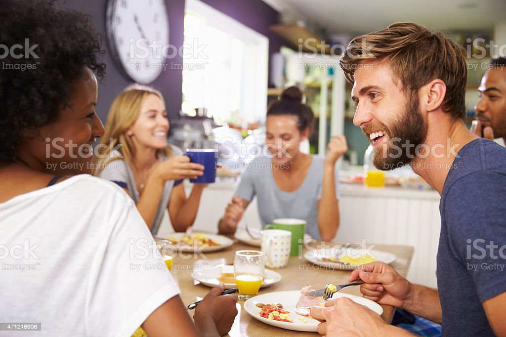 A group of friends enjoying a hearty breakfast meal together stock photo
