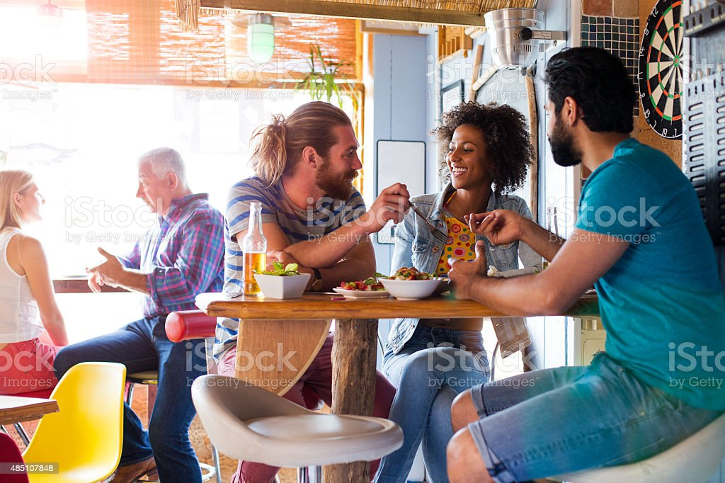 Group of Friends Enjoying a Meal with a Drink stock photo