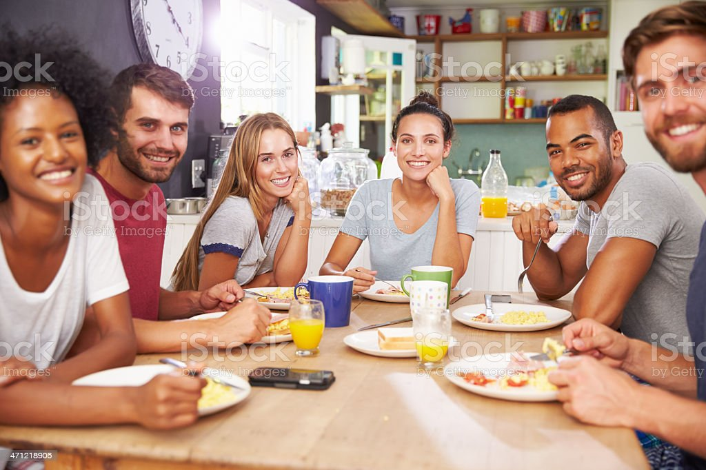 Group Of Friends Enjoying Breakfast In Kitchen Together stock photo
