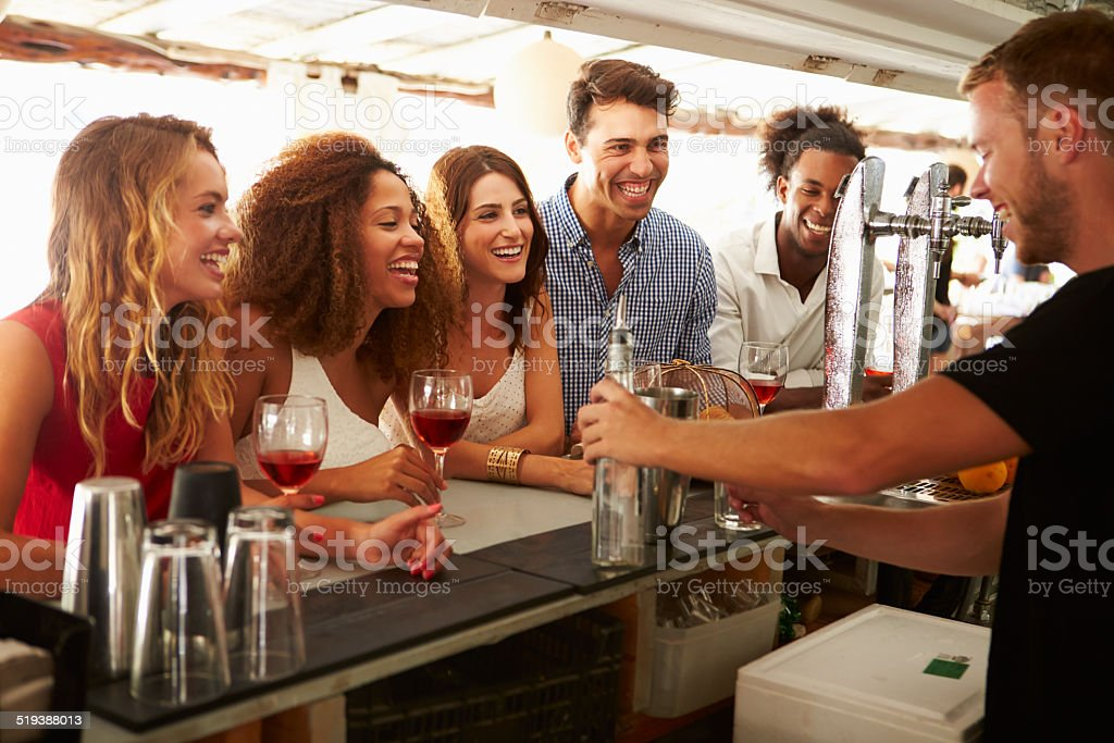 Group Of Friends Enjoying Drink At Outdoor Bar stock photo