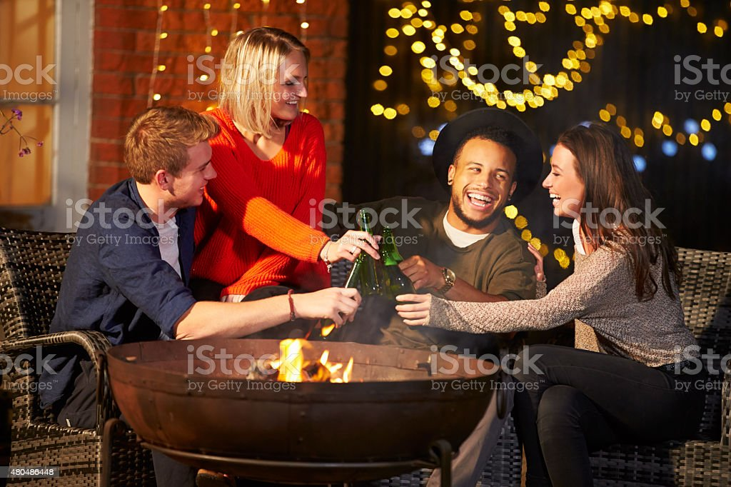 Group Of Friends Enjoying Evening Drinks By Firepit stock photo