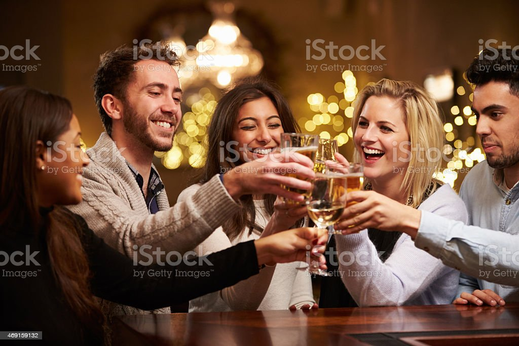 Group Of Friends Enjoying Evening Drinks In Bar stock photo