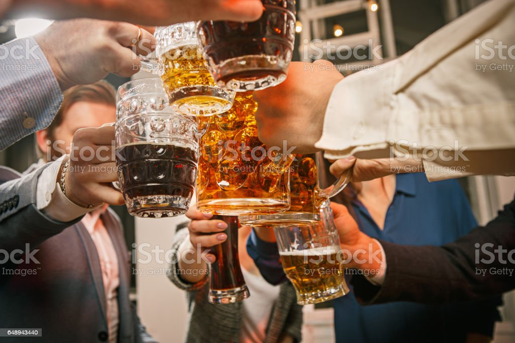 Group of friends enjoying evening drinks with beer stock photo