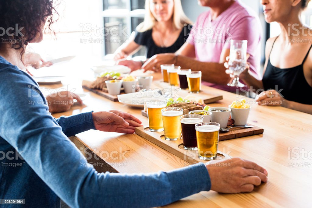 Group Of Friends Enjoying Lunch & Craft Beer Tasting stock photo