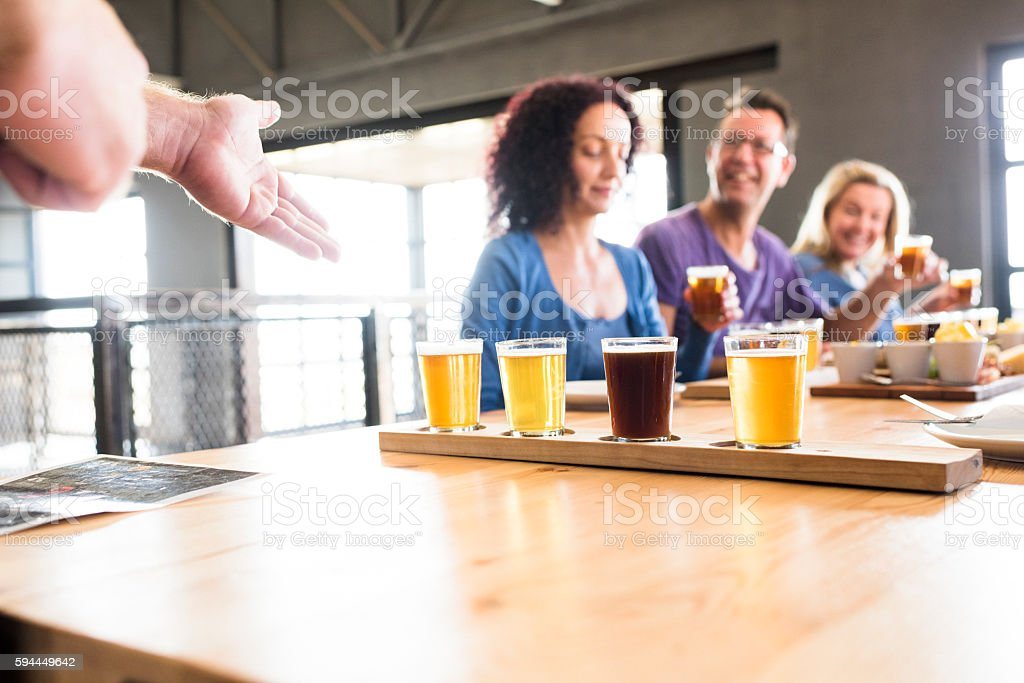 Group Of Friends Enjoying Lunch Together At A Brewery stock photo