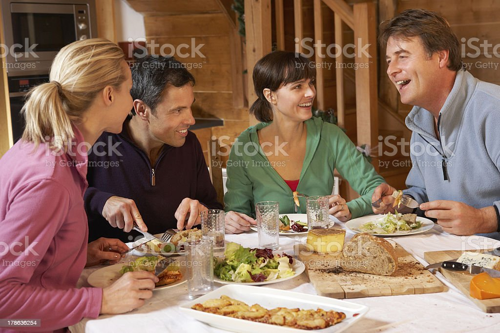 Group Of Friends Enjoying Meal In Alpine Chalet Together stock photo
