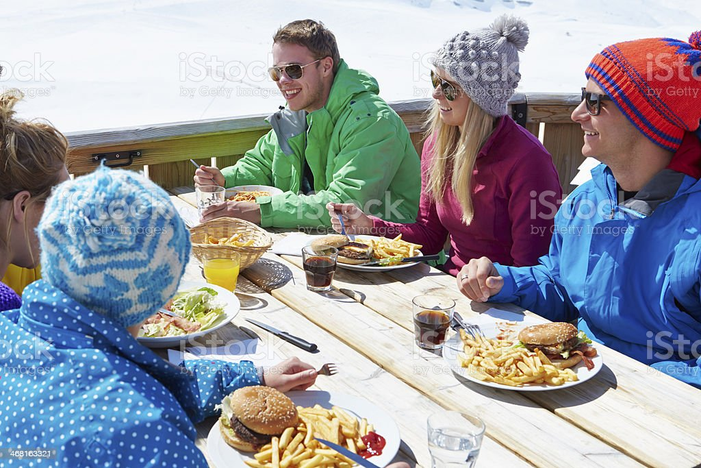 Group Of Friends Enjoying Meal In Cafe At Ski Resort stock photo