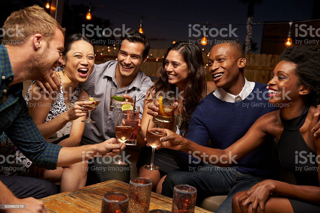 Group Of Friends Enjoying Night Out At Rooftop Bar stock photo