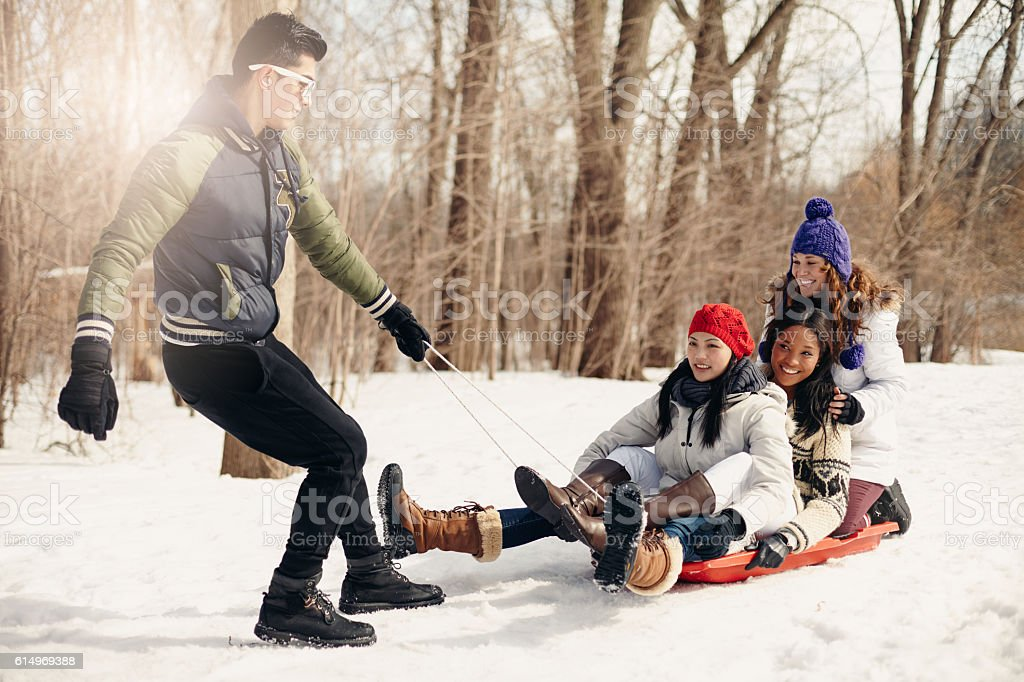Group of friends enjoying pulling a sled in the snow stock photo