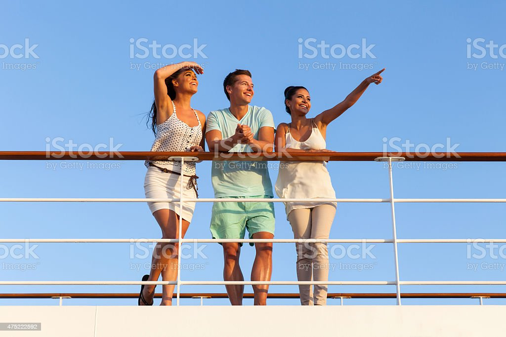 group of friends enjoying sunset on cruise stock photo
