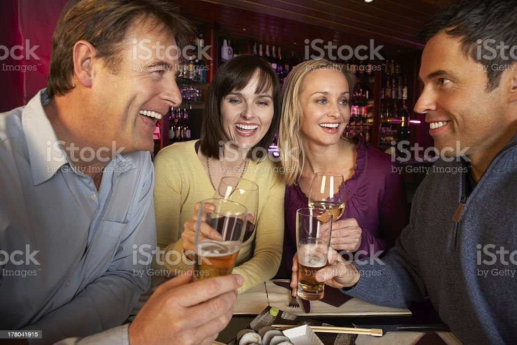 Group Of Friends Enjoying Sushi In Restaurant stock photo