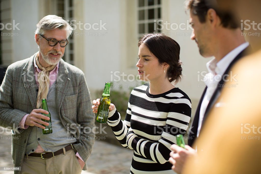 Group of friends enjoying time in a garden. stock photo