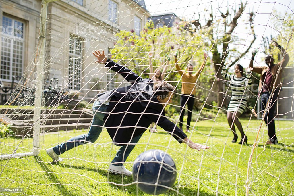 Group of friends enjoying time in a garden playing football stock photo