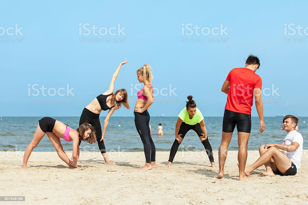 Group Of Friends Exercising On Beach royalty-free stock photo