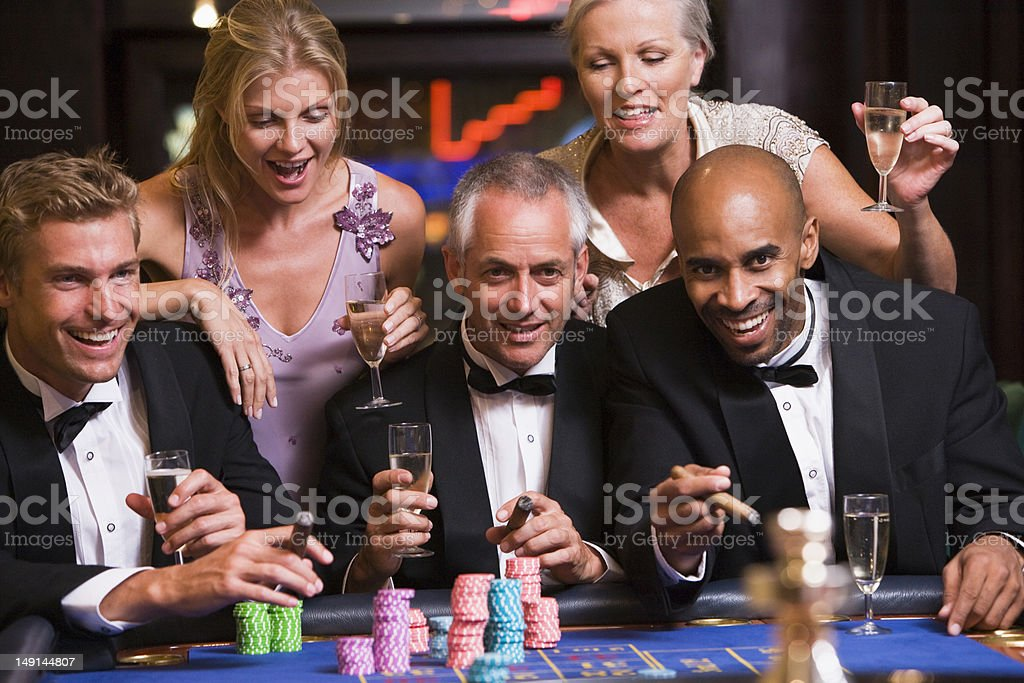 Group of friends gambling at roulette table royalty-free stock photo