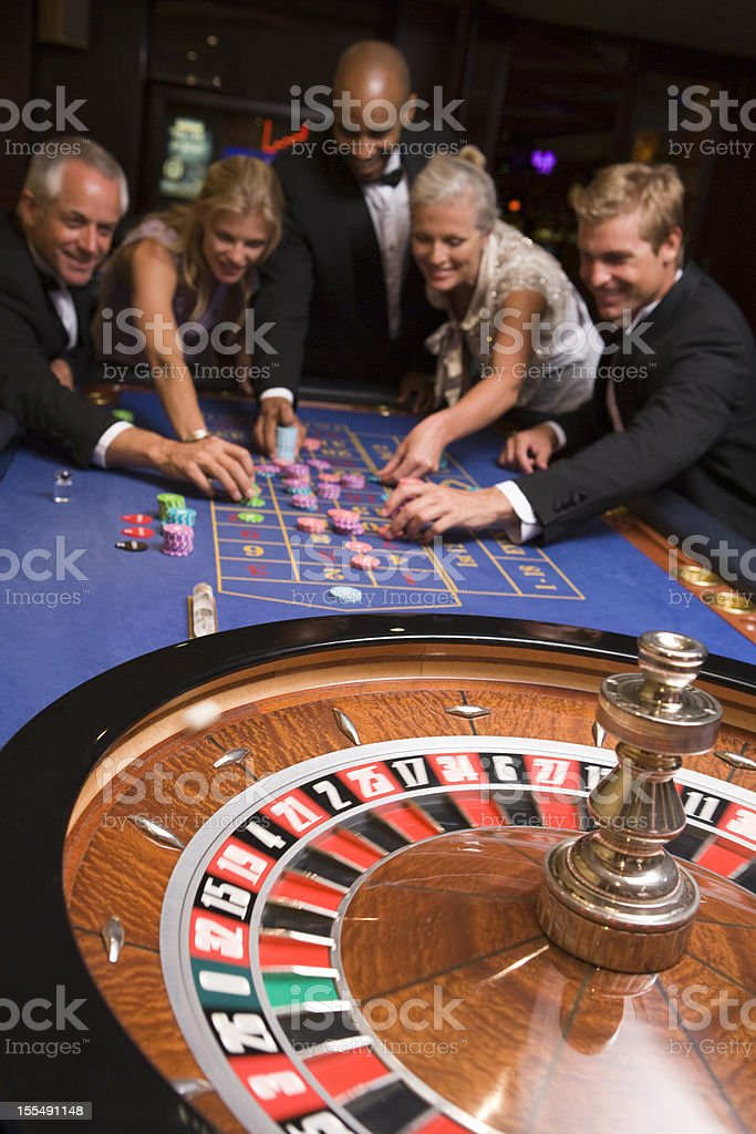 Group of friends gambling in casino stock photo
