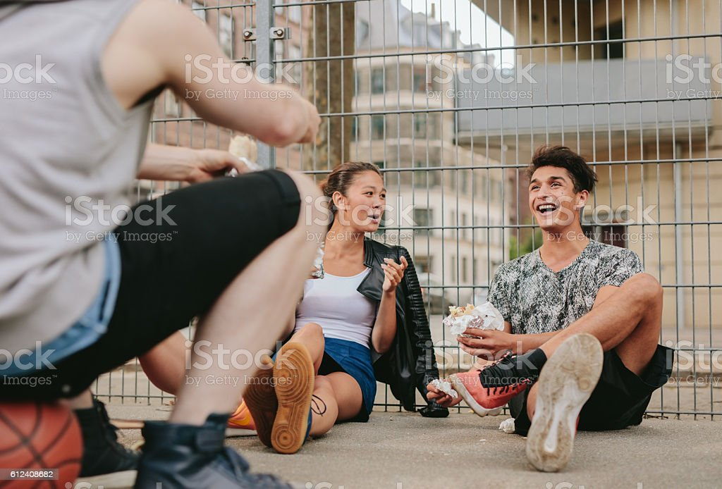 Group of friends hanging out on basketball court stock photo