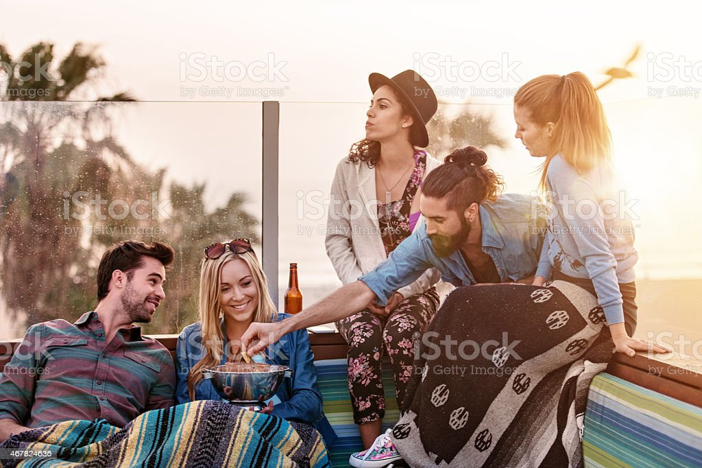 Group of friends hanging out on rooftop stock photo