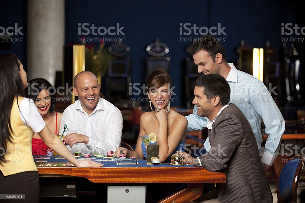 A group of friends happily playing cards in a casino stock photo