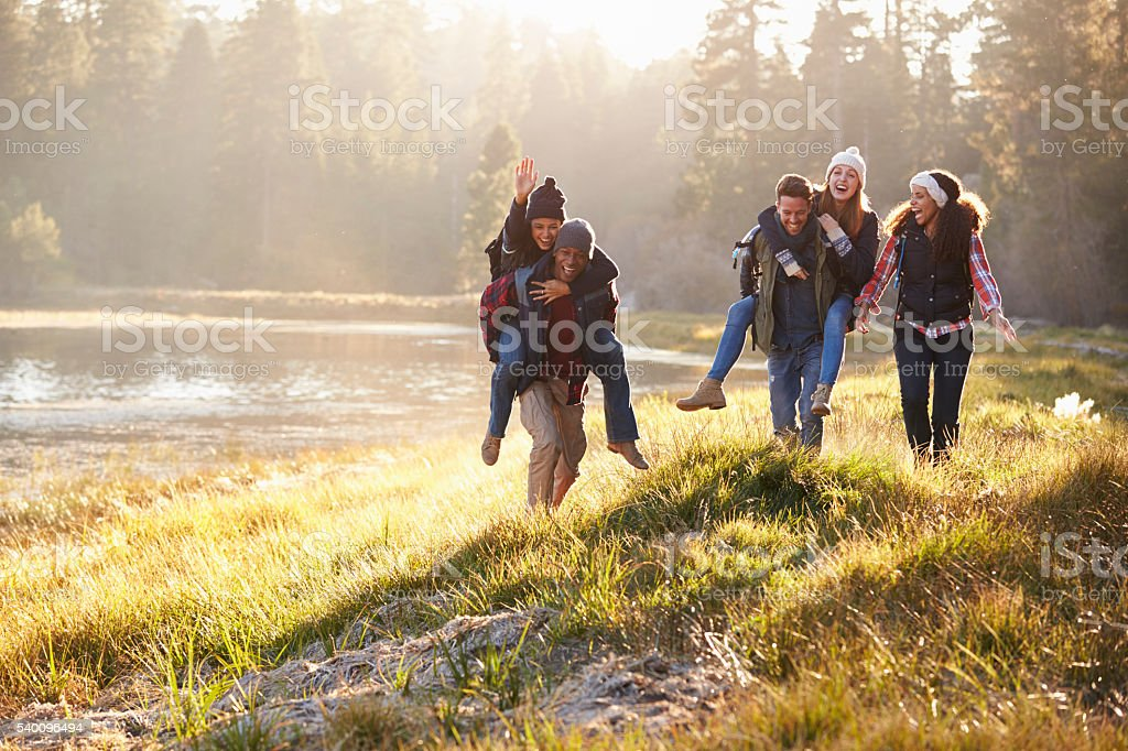 Group of friends have fun piggybacking by a lake stock photo