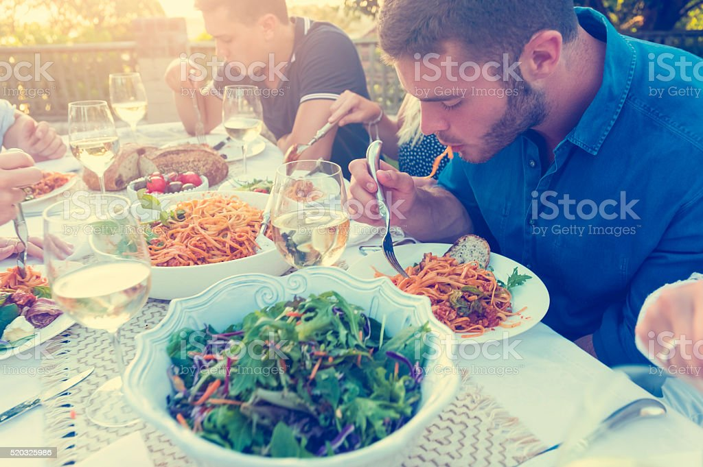 Group of friends having a meal outdoors. stock photo